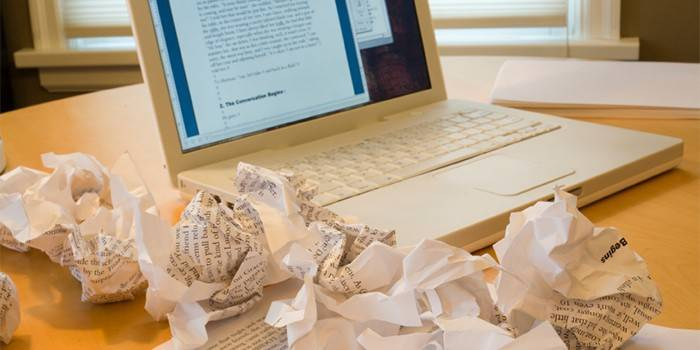 Ноутбук и смятые листы бумаги